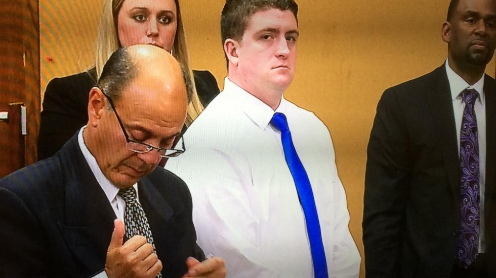 Michael Brelo stands with his defense team at the end of the trial's opening day.