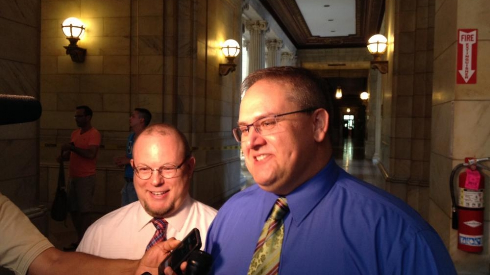 Keith Garrett talks to reporters as his partner, Christopher Richardson, smiles behind him. The two were the first same-sex couple to be married in Cuyahoga County. Photo by Caleigh Wells