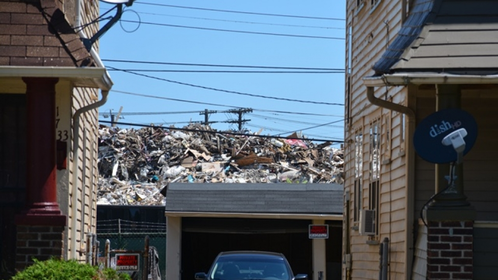 A pile of debris from demolished houses rises behind a row of homes in East Cleveland.