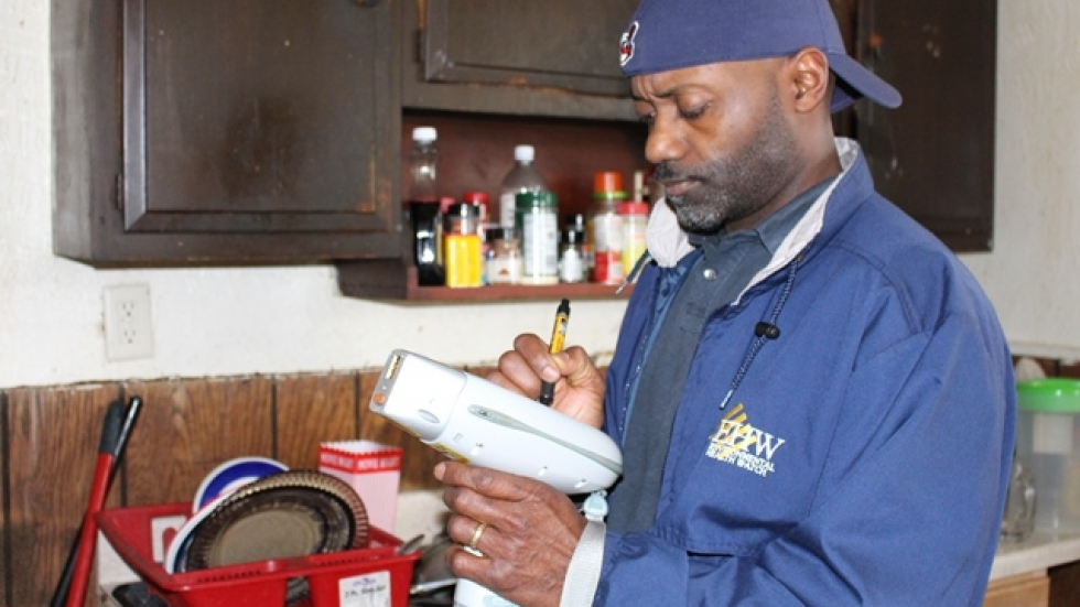 Akbar Tyler, a home inspector with Environmental Health Watch, examines a house for lead.
