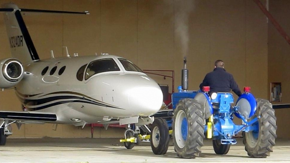 A tractor tows a corporate jet out of a hangar at Northeast Ohio Regional Airport [photo: Brian Bull/ideastream]