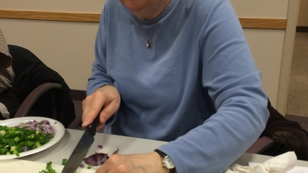 Breast cancer survivor Kathy Dietrich chops green onions and learns about healthy eating at The Gathering Place.