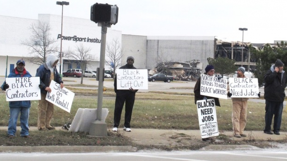 Members of the Black and Minority Contractors picket as much of the Randall Park Mall is being razed behind them.