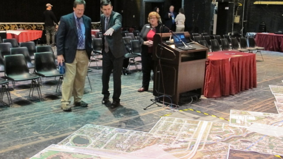 Dan Rice (L) and Josh Sikich look over aerial photographs of the towpath on the stage of Akron Civic Theater