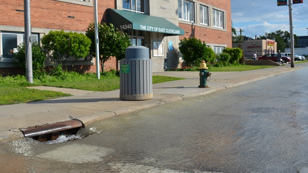 Water from a broken pipe pours into a storm drain outside East Cleveland city hall in 2014.