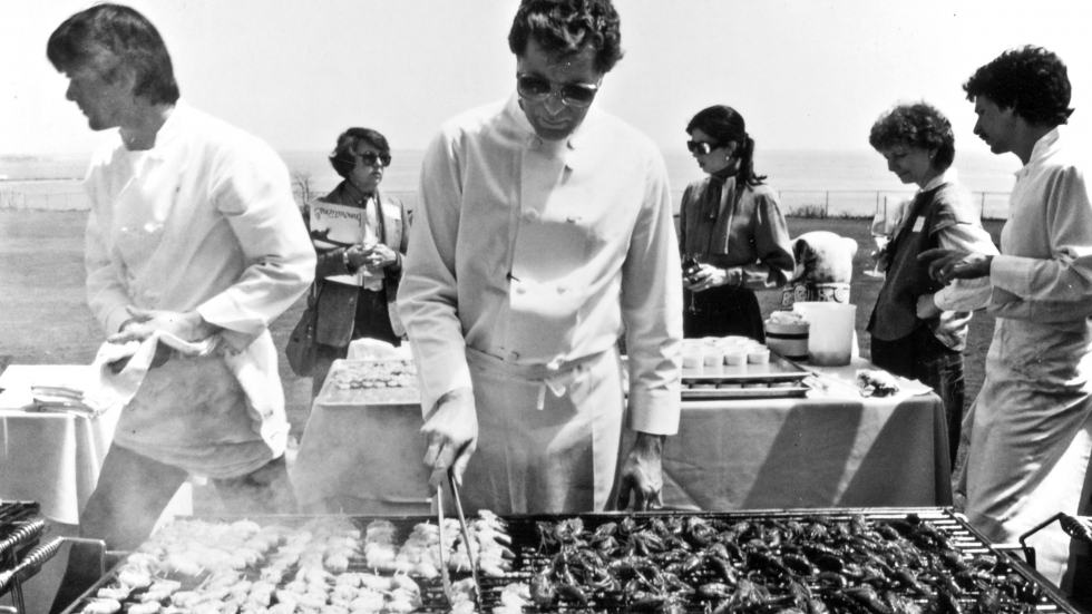 """Jeremiah Tower <a href=""""http://www.csmonitor.com/1983/0518/051807.html"""">grills lunch</a> for 100 food journalists on the lawn of the Astor mansion in Newport Beach, R.I., in 1983. Tower wowed the East Coasters with his """"new California"""" or new American cooking."""