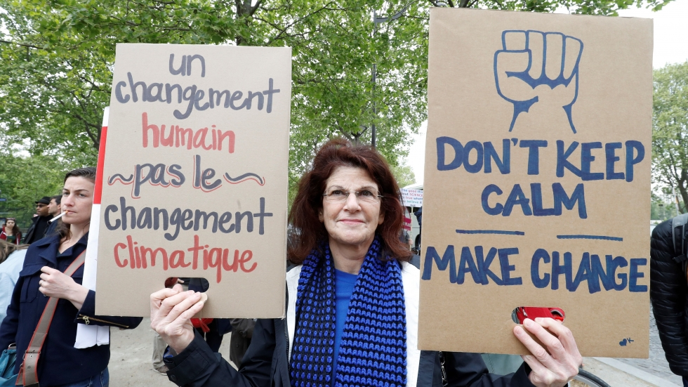 """People take part in the March for Science in Paris. The sign reads: """"A human change, not a climate change"""""""