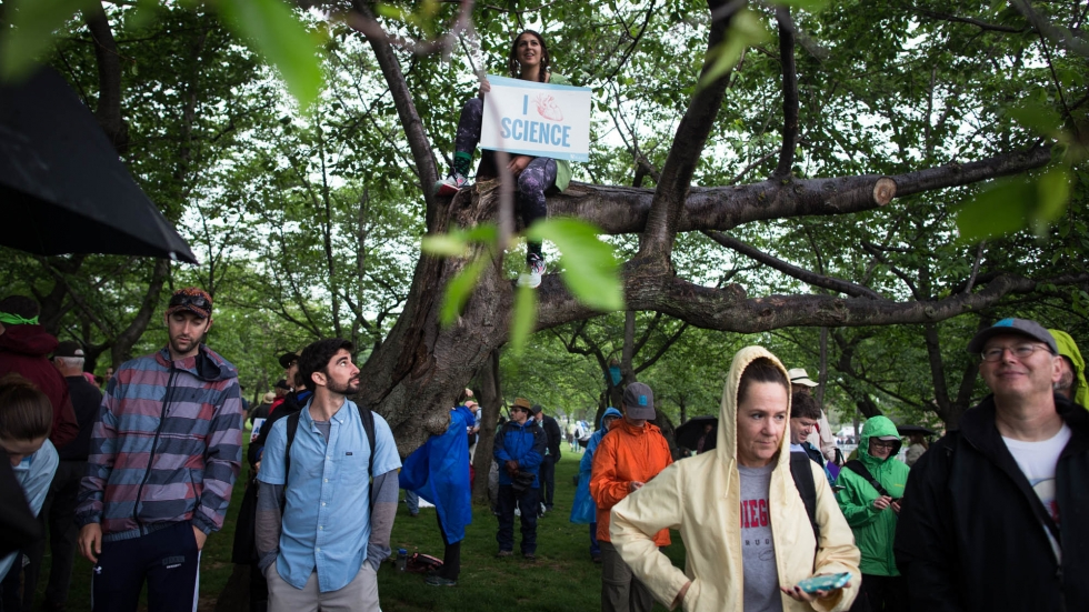 Participants seek cover from the rain to watch the rally.