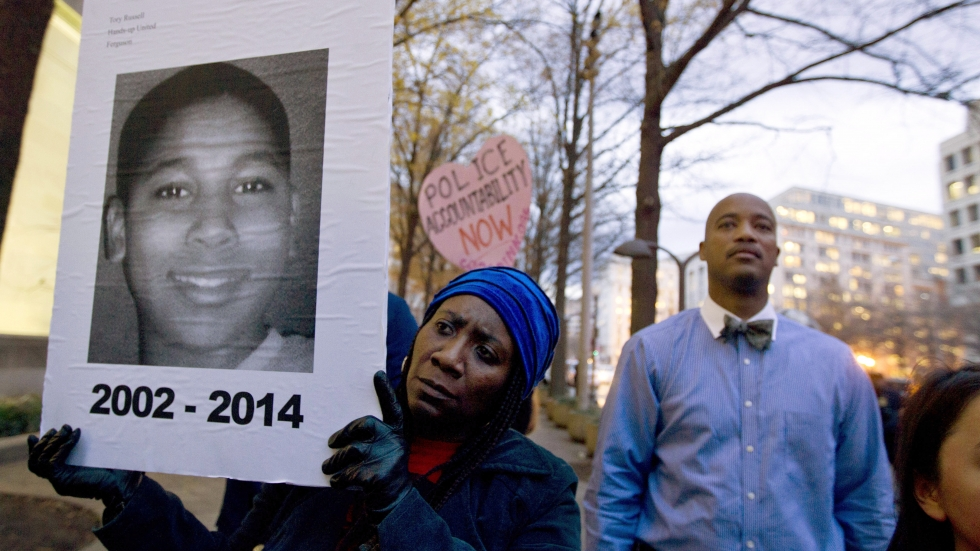 Tomiko Shine holds up a picture of Tamir Rice during a 2014 protest in Washington, D.C. Timothy Loehmann, the police officer who shot and killed the 12-year-old boy, was fired Tuesday for answers he provided on his personal history statement during the hiring process.