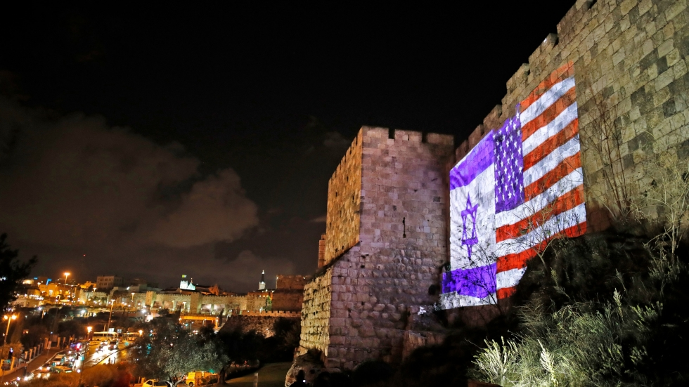 """The American and Israeli flags are on display Wednesday on the walls of the Old City of Jerusalem. President Trump announced that the U.S. will view Jerusalem as the capital of Israel, and he ordered the State Department to """"begin preparation to move the American Embassy from Tel Aviv."""" The controversial move threatens to unsettle the region's volatile politics."""