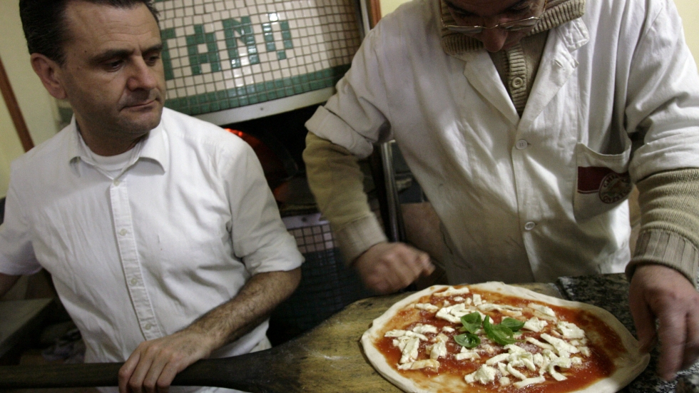 A pizza is prepared at a restaurant in downtown Naples. On Wednesday, the traditional art of pizza-making was given UNESCO cultural heritage status.