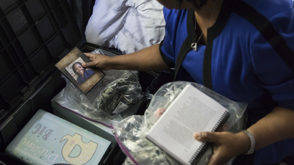 Wanda Irving holds a photograph from the funeral of her late daughter Shalon Irving as she goes through a trunk full of her mementos and possessions. She plans to keep the trunk for when her granddaughter Soleil gets older.