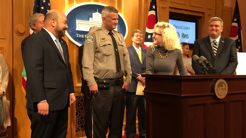 Daisy Tolliver smiles at Waverly Police Capt. Dennis Crabtree at a news conference with House Speaker Cliff Rosenberger (R-Clarksville, right) and Rep. Scott Ryan (R-Granville).