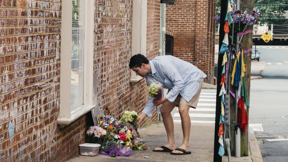 Peter Reijmers, 29, of Charlottesville, Va lays flowers at a memorial on 4th street SE where Heather Heyer's was killed last August.