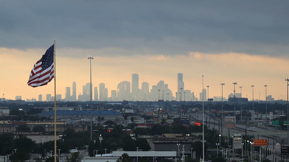 The Houston skyline with a US flag in the foreground and the skyscrapers of downtown in the distance.