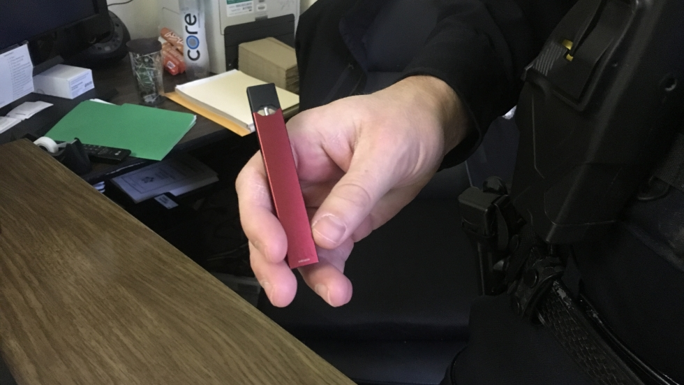 North High School resource officer Kevin Evans holds a juul, an e-cigarette device popular with high school students.