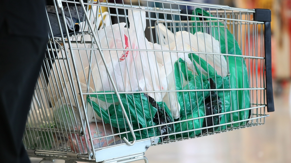 A shopping cart full of plastic bags.