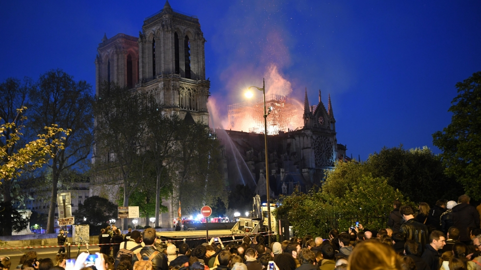 Crowds look on as flames and smoke billow from the cathedral's roof.