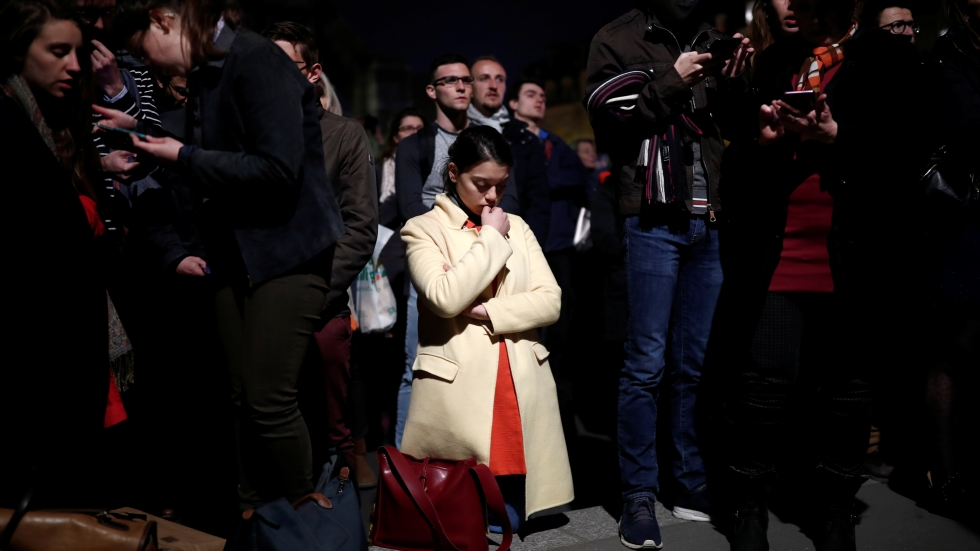 A woman prays next to Notre Dame after it suffered heavy damage from Monday's fire.
