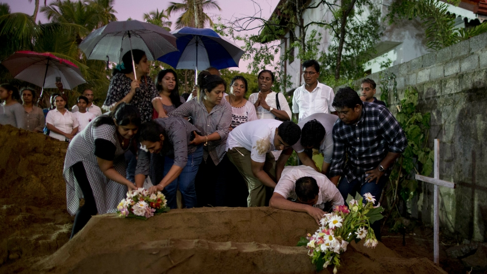Relatives place flowers after the burial of three victims of the same family, who died at Easter Sunday bomb blast at St. Sebastian Church in Negombo, Sri Lanka, on Monday.