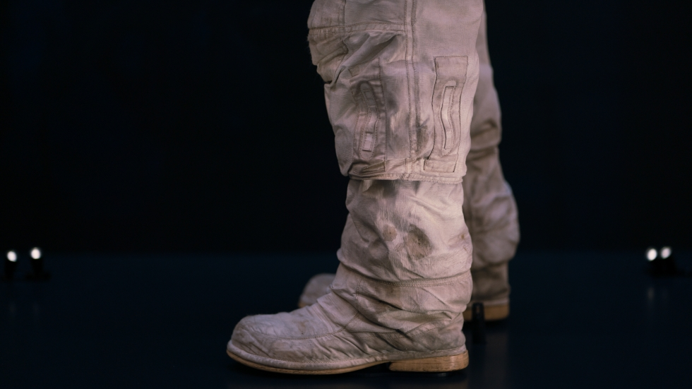 The thighs, knees and boots of the spacesuit are stained with lunar dust.