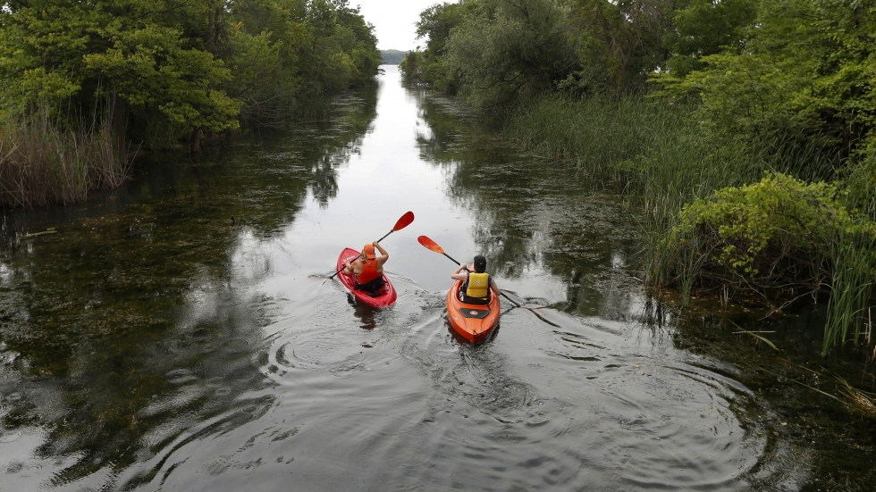 Kayakers paddle in a canal leading to the Detroit River in Detroit, Mich. Temperatures are soaring across much of the U.S. this week.