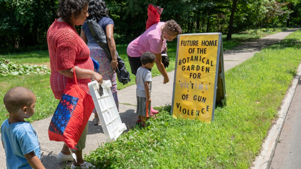 Three of the mothers spearheading the development of the New Haven Botanical Garden of Healing Dedicated to Victims of Gun Violence take a look at the temporary sign they created after a few hours of work in the garden.