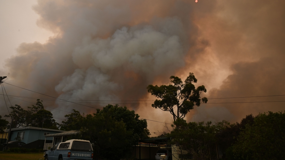 A fire burns from back-burning as firefighters prepare ahead of a fire front in the New South Wales town of Jerrawangala on New Year's Day. A major operation to reach thousands of people stranded in fire-ravaged seaside towns was under way in Australia.