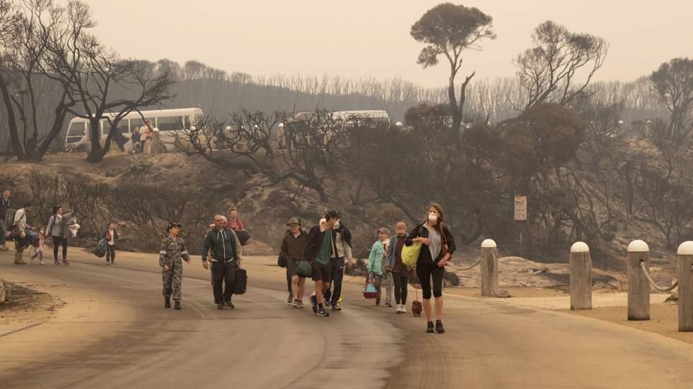 Evacuees walk to the beach at Mallacoota in Victoria to board vessels and be ferried out.