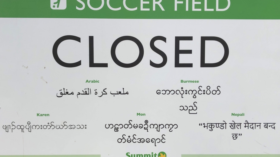 A closed sign in multiple languages shows the diversity of the immigrant populations affected by the coronavirus crisis.