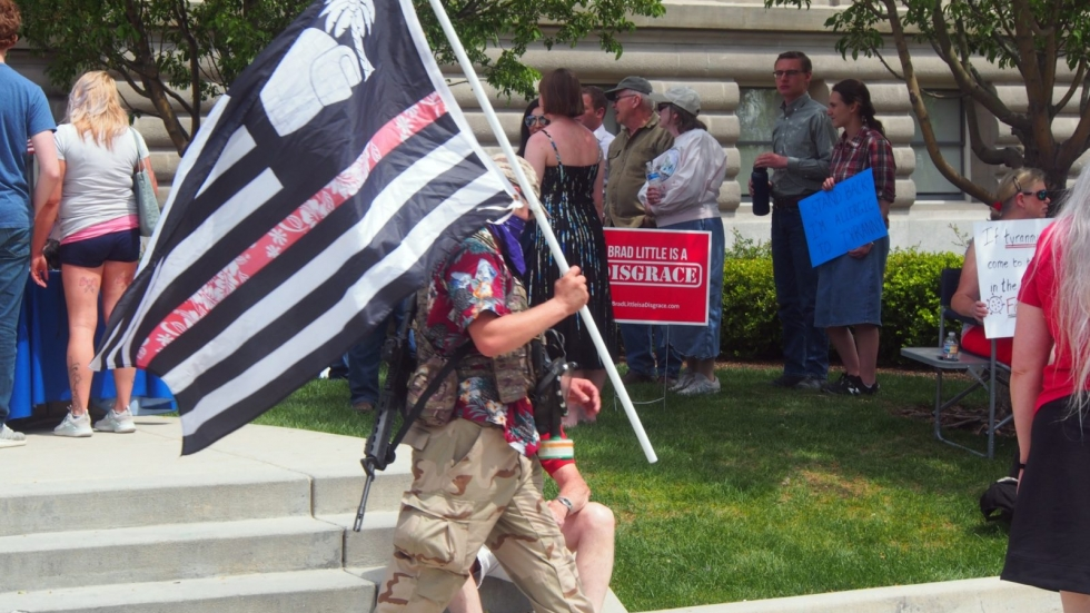 """An armed protester at an anti-stay-at-home rally in Boise, Idaho, on May 2 carries a flag that represents """"The Boogaloo,"""" a nickname used by anti-government movements to signify what they see as a looming second civil war in America."""