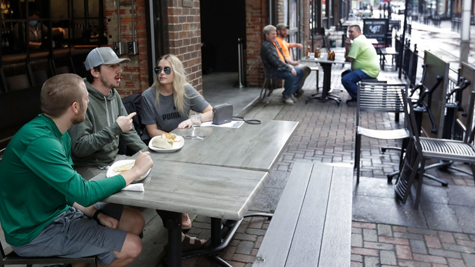 Mike Kapeluck, left to right, Michael Cole, and Ashley Healy have lunch outside of the The Corner Alley during the coronavirus pandemic, Friday, May 15, 2020, in Cleveland.