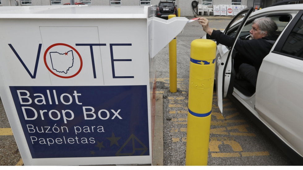 A man drops off his absentee ballot during Ohio's 2020 primary at a ballot box in Cleveland.