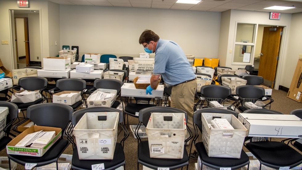 Election official Jim Fortner places a crate of sorted absentee ballots with others from the same ward at the Madison, Wis., City-County Building on Aug. 5, 2020. Delays and failure to deliver absentee ballots in Wisconsin and other key swing states have sparked concerns about how well the November presidential election will be managed during the pandemic.