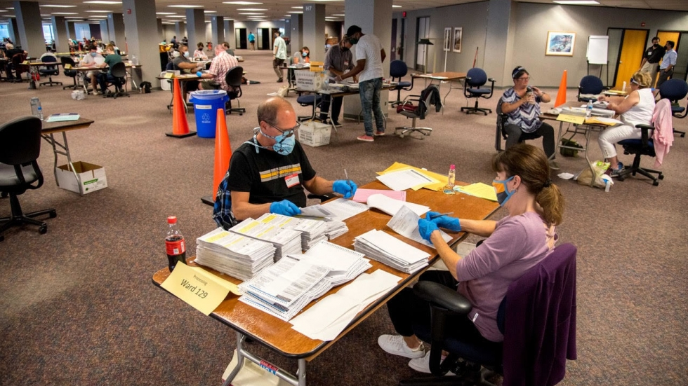 """Election workers Jeff and Lori Lutzka process absentee ballots at Milwaukee's """"central count"""" location on August 11, 2020."""