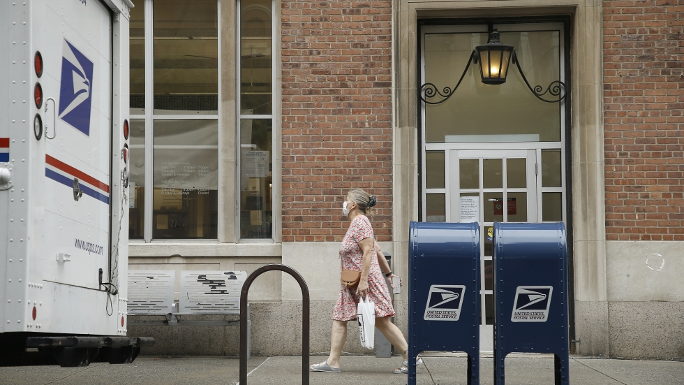 A woman walks past two USPS mailboxes near a post office on August 16, 2020, in New York City.