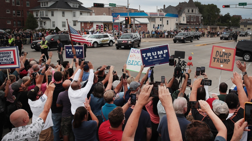 Trump supporters and Trump protesters watch as the motorcade carrying President Donald Trump passes by on Sept.1 in Kenosha, Wis.