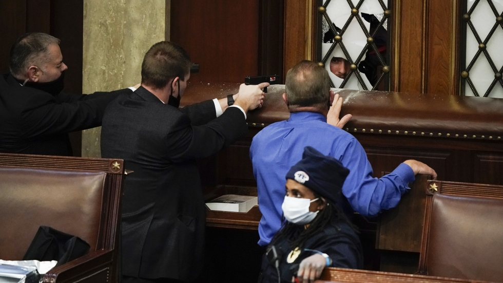 Police with guns drawn face off with protesters trying to break into the House chamber Wednesday at the Capitol.