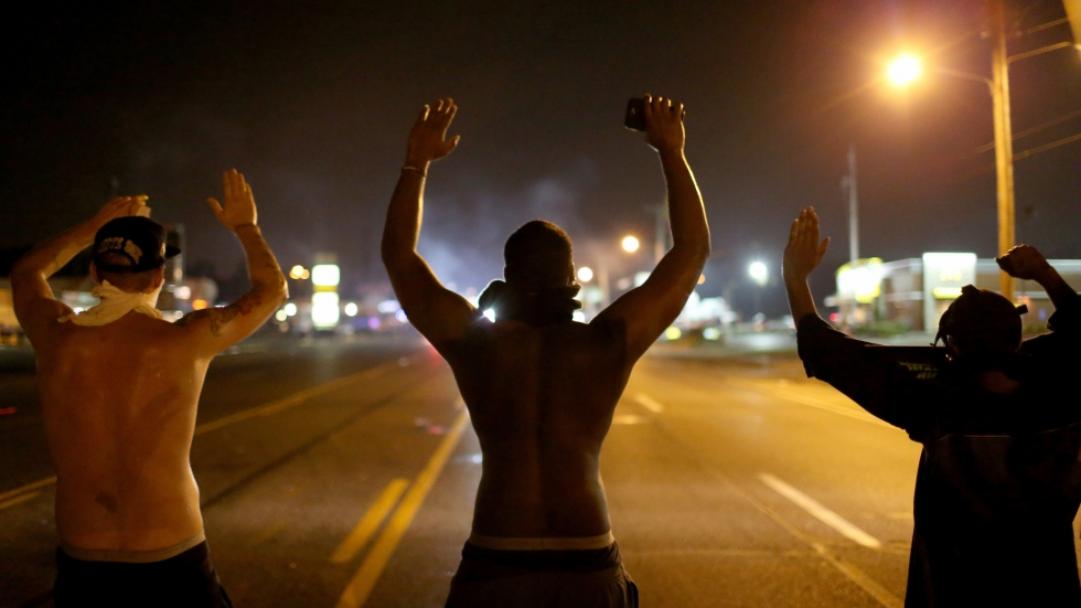 """Demonstrators raise their arms and chant, """"Hands up, don't shoot"""" on Aug. 17, 2014, as they protest the shooting death of Michael Brown in Ferguson, Mo."""