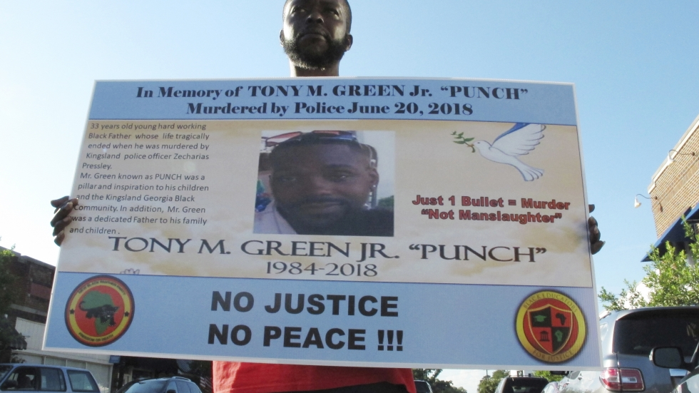 Tony White holds a sign showing a photograph of his slain cousin, Tony Green, outside Kingsland City Hall in Kingsland, Ga. Authorities say Green was fatally shot in 2018, while he fled Kingsland police officer Zechariah Presley.