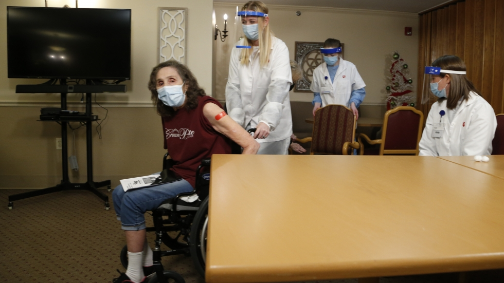 Crown Pointe Care Center resident Rebecca Meeker, left, rolls away from the table after receiving a COVID-19 vaccine Friday, Dec. 18, 2020, in Columbus, Ohio. Meeker was the first long-term care patient in Ohio to receive a vaccine.