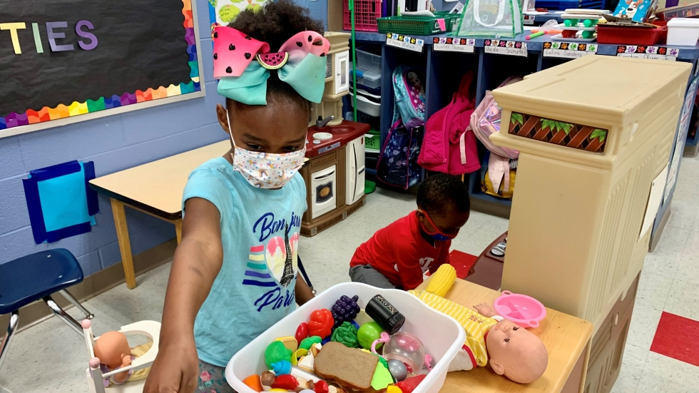 """Aamilah Culler takes a break from caring for her stuffed hedgehog to care for her baby doll and critique a classmate's plastic-pizza choices. In recent weeks, Canton has allowed the children to get a bit closer together during """"brain breaks"""" at play stations."""