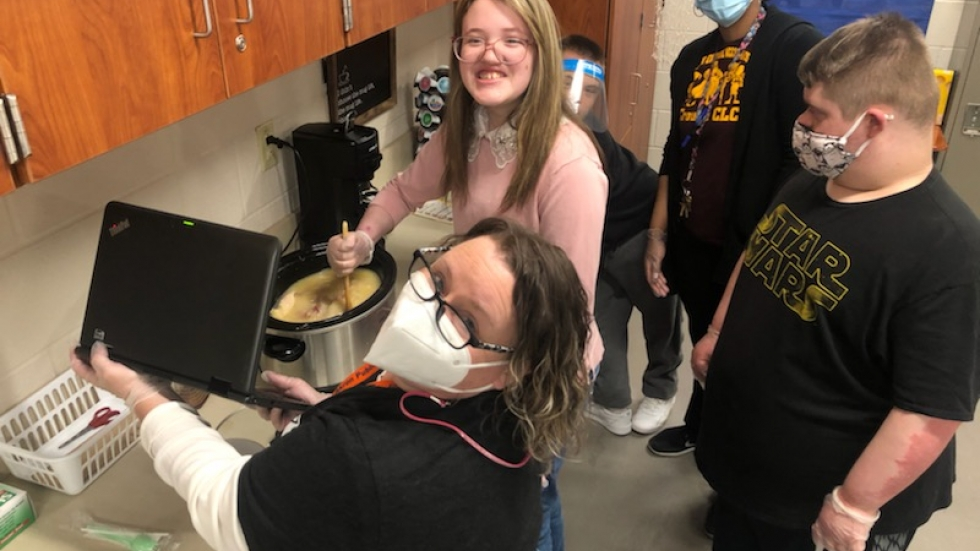Conni Zeno, an intervention specialist at Ellet High School in Akron, surrounded by students and a staff member, holds up a computer so that her remote students can participate in a class cooking demonstration