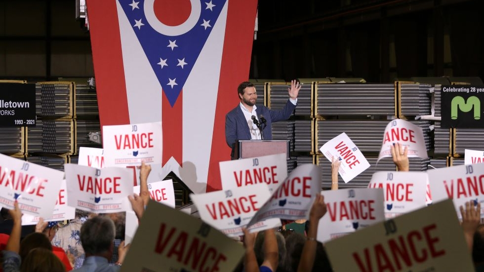 """J.D. Vance in his hometown of Middletown Thursday night with an Ohio state flag behind him and a sea of """"Vance"""" signs being held up by the crowd in the foreground"""