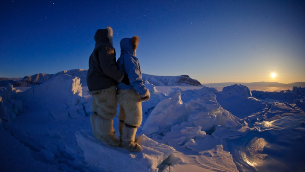 As the moon rises, Florian and his wife, Emil, are kept warm by traditional polar bear clothing provided by their Native hosts.