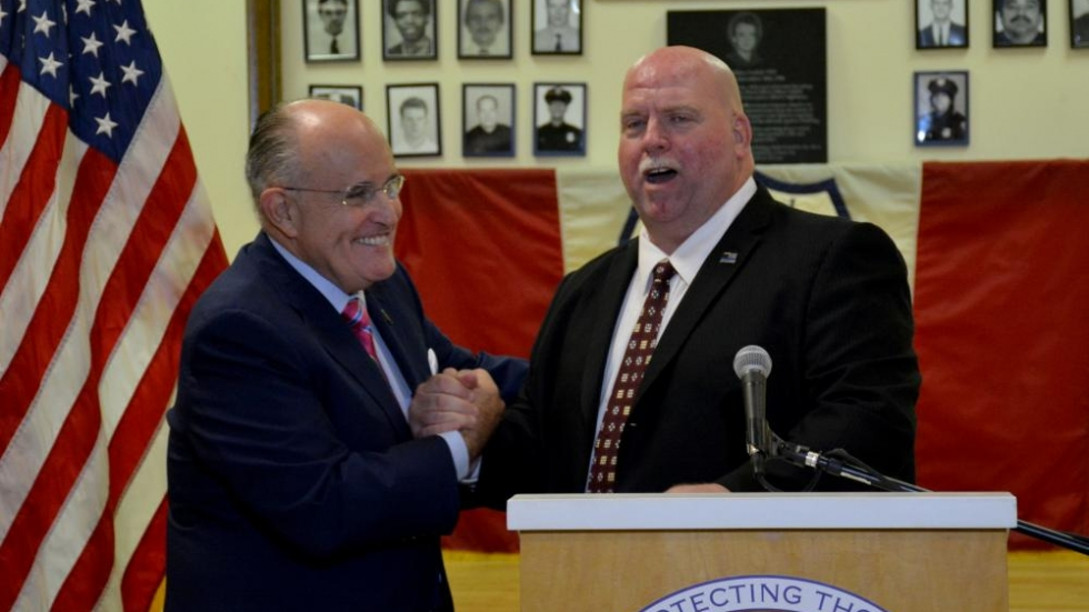 Cleveland police patrolmen's union President Steve Loomis shakes hands with Rudy Giuliani.