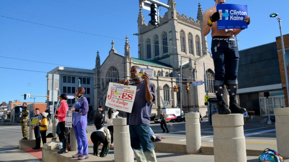People hold signs for candidates at a bus stop across from the board of elections in Cleveland.
