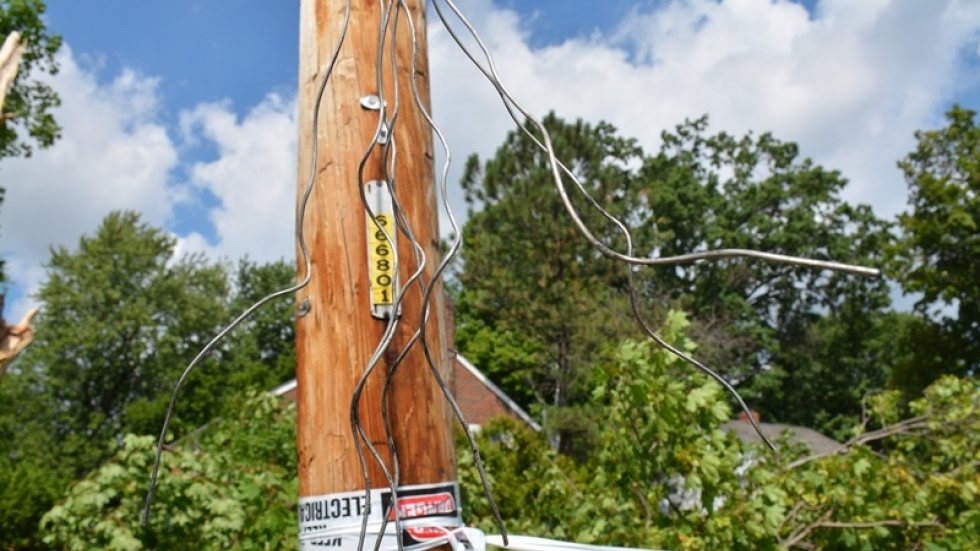 A damaged utility pole is marked off with tape.
