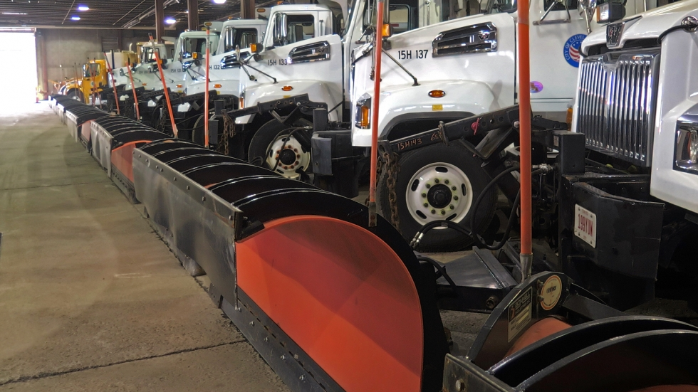Snow plows lined up in a warehouse.