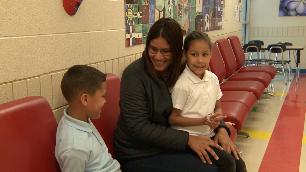 Madalyn Rosario sits with two of her three children in the lobby of Thomas Jefferson Elementary School. The family moved to Cleveland from Puerto Rico in October after Hurricane Maria devastated the island. (Ashton Marra/ideastream)